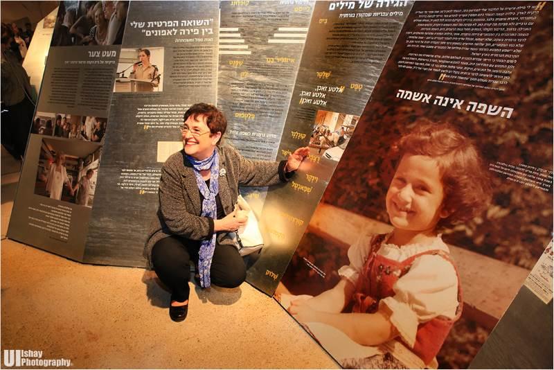 רותי אופק לצד תמונת ילדות שלה עם העלייה ארצה מוינה המוצגת בתערוכה|צילום: UI-ishay photography